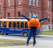 Otto with arms raised in front of 'Cuse Trolley driving in front of Tolley Building